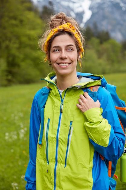 Optymistyczna, Kochana Podróżniczka O Radosnym Wyrazie Twarzy, Ubrana W Niebiesko-zieloną Kurtkę, Nosi Plecak Darmowe Zdjęcia