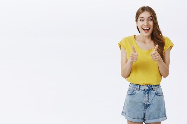 Optymistyczna Piękna Dziewczyna Z Aprobatą Pokazuje Kciuki Do Góry, Lubi Pomysł, Zgadza Się Lub Poleca Coś Niesamowitego Darmowe Zdjęcia