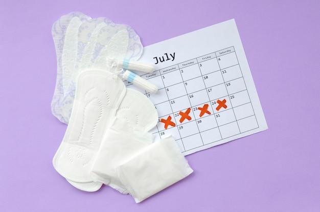 Opuszki Menstruacyjne I Tampony W Kalendarzu Miesiączkowym Leżały Płasko Premium Zdjęcia