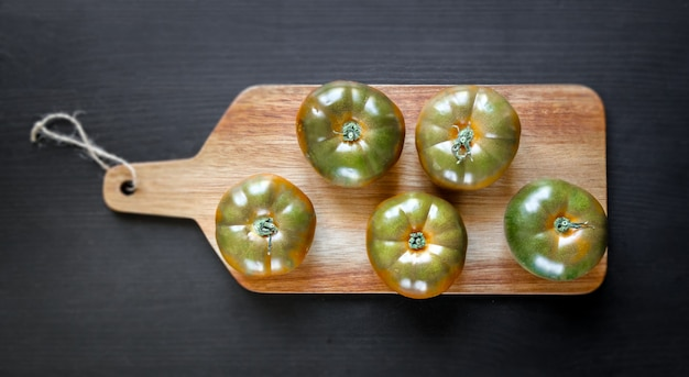 Organiczne Pomidory Black Krim Na Drewnianej Desce Do Krojenia Premium Zdjęcia