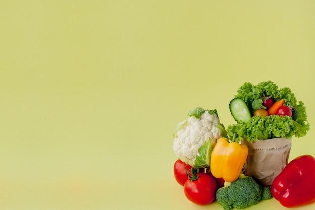 Organiczne Warzywa Brokuły Ogórki Papryka Jabłka W Brązowym Papierze Torba Spożywcza Kraft Na żółtym Tle. Zdrowa Dieta Błonnik Pokarmowy Wegańskie Pojęcie Bez Plastiku. Baner Plakatowy Premium Zdjęcia