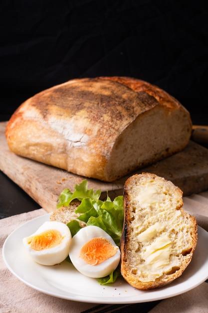 Organiczny Rzemieślniczy Chleb Na Zakwasie I Jajka Na Twardo W Białej Płytce Premium Zdjęcia