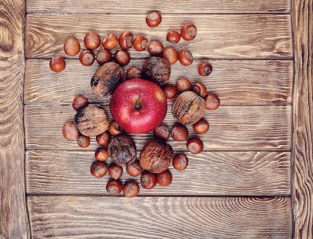 Orzechy I Jabłko Na Drewnianym Stole, Skupić Się Na Jabłku Pośrodku Premium Zdjęcia