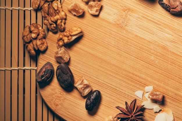 Orzechy, Owoce, Ziarna Kakaowe I Przyprawy Anyżowe Na Tle Deski Do Krojenia Premium Zdjęcia