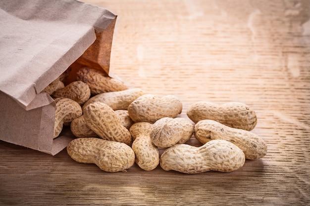 Orzeszki Ziemne Papierowa Torba Na Drewnianej Desce Pojęcie Jedzenia I Picia Premium Zdjęcia