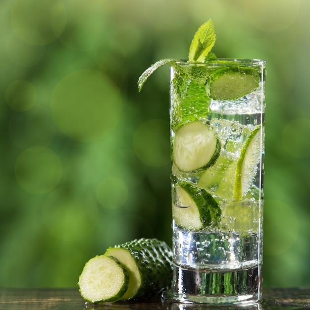 Orzeźwiający Letni Napój Gazowany W Szklance Z Dodatkiem Limonki I Plasterków świeżego Ogórka Na Tle Zieleni Premium Zdjęcia