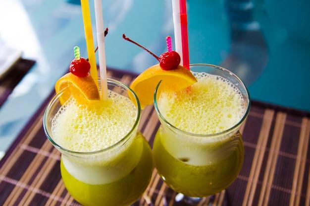 Orzeźwiający żółty Napój Z Pomarańczą, Wiśnią I Lodem W Restauracji Na Stole Premium Zdjęcia