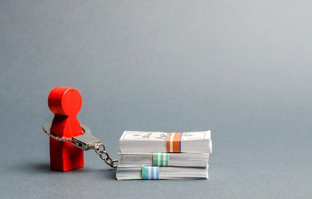 Osoba jest skuta kajdankami ze stosem pieniędzy. człowiek jest uzależniony od pieniędzy, zakupoholiczka Premium Zdjęcia