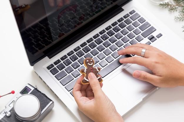 Osoba Korzystająca Z Laptopa I Jeść Ciasteczka Premium Zdjęcia