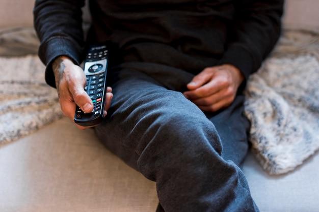 Osoba korzystająca z pilota podczas siedzenia na kanapie Darmowe Zdjęcia