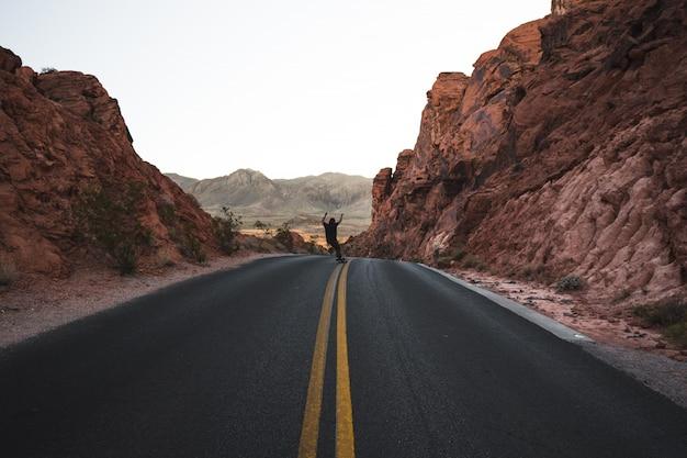 Osoba Na łyżwach Na Autostradzie W Otoczeniu Czerwonych Skał Darmowe Zdjęcia