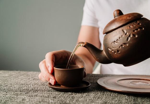 Osoba nalewająca ciepłą herbatę w filiżance Darmowe Zdjęcia