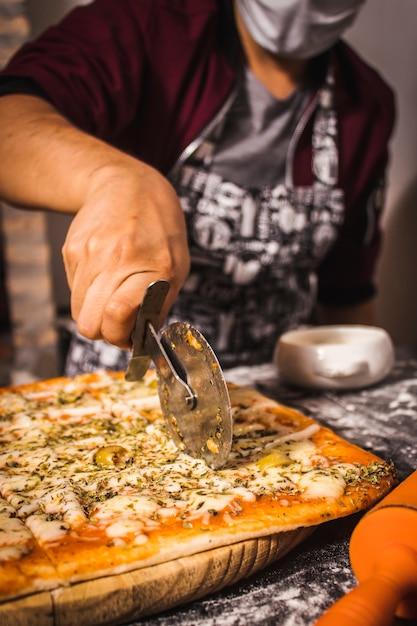 Osoba Nosząca Maskę I Krojąca W środku Pizzę Premium Zdjęcia