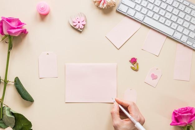 Osoba pisze na papierze przy stołem z różami Darmowe Zdjęcia