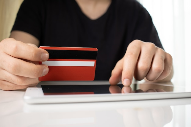 Osoba Posiadająca Czerwoną Kartę Kredytową Na Tablecie Na Białej Powierzchni Darmowe Zdjęcia