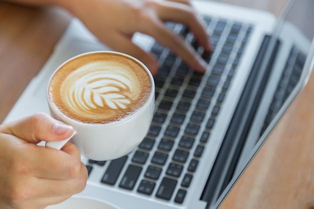 Osoba Pracująca Na Laptopie Z Filiżanką Kawy Obok Darmowe Zdjęcia
