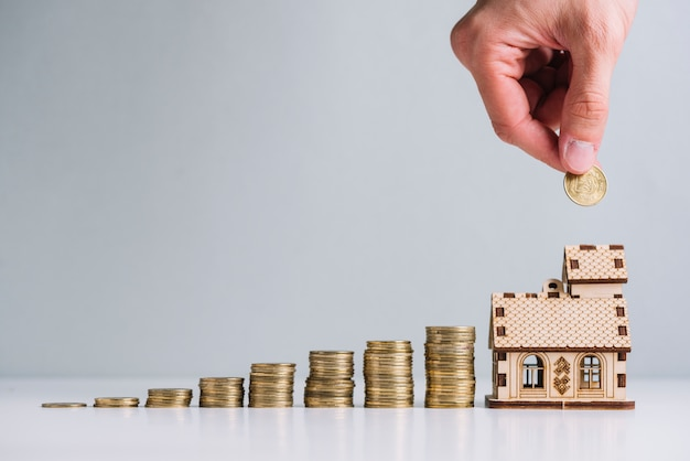 Osoba ręka inwestuje pieniądze w kupienie domu Darmowe Zdjęcia