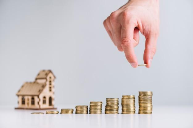 Osoba ręka układa monety przed modelem domu Darmowe Zdjęcia