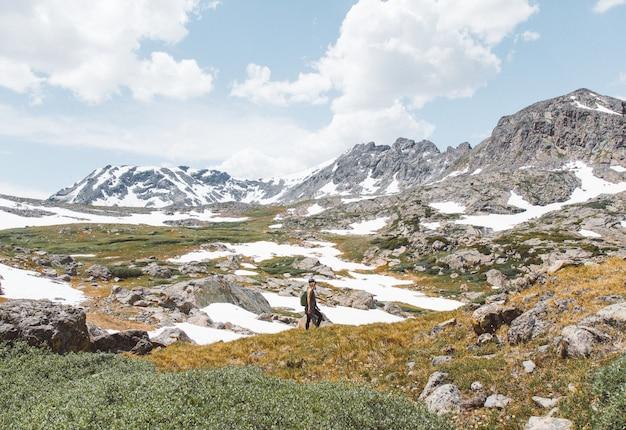 Osoba Stoi Blisko Góry Pod Chmurnym Niebem Przy Dniem Darmowe Zdjęcia