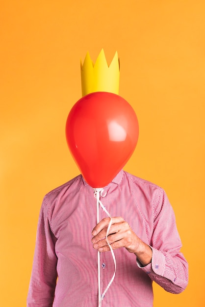 Osoba Trzyma Balon Na Pomarańczowym Tle Darmowe Zdjęcia