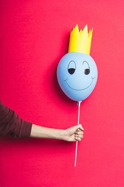 Osoba Trzyma Błękitnego Balon Na Czerwonym Tle Z Kopii Przestrzenią Darmowe Zdjęcia