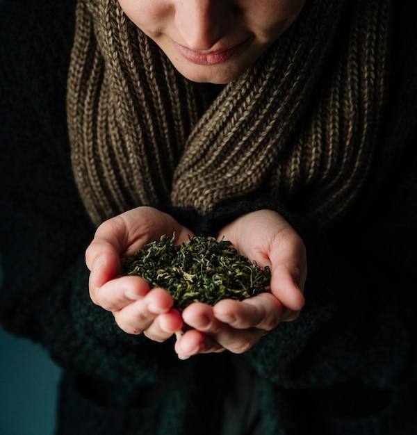 Osoba trzyma herbaciane zioła i jest ubranym szalika Darmowe Zdjęcia