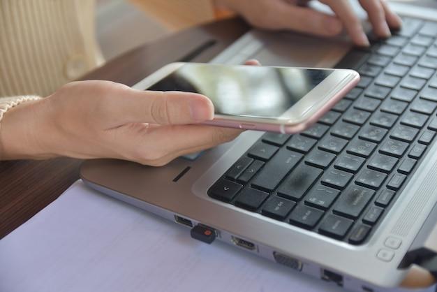 Osoba Trzyma Telefon Komórkowy I Korzysta Z Laptopa Premium Zdjęcia