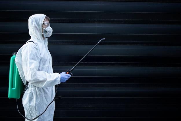 Osoba W Białym Kombinezonie Chroniącym Przed Chemikaliami Trzymająca Rozpylacz Ze środkami Dezynfekującymi W Celu Powstrzymania Rozprzestrzeniania Wysoce Zaraźliwego Wirusa Darmowe Zdjęcia