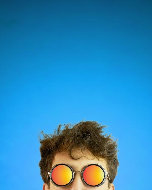 Osoba w okulary przeciwsłoneczne z rozczochrane włosy na niebieskim tle gradientu Premium Zdjęcia