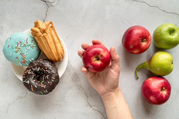 Osoba Wybiera Owoc Nad Ciasteczka Jedzeniem Przeciw Betonowemu Tłu Darmowe Zdjęcia