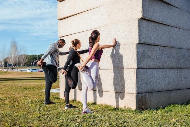 Osobisty trener rozciągający się z dwoma dziewczynami Premium Zdjęcia