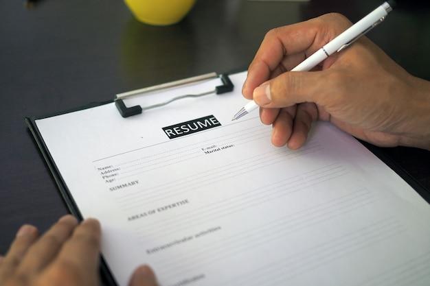 Osoby poszukujące pracy, mężczyźni wypełniają cv na formularzu. Premium Zdjęcia