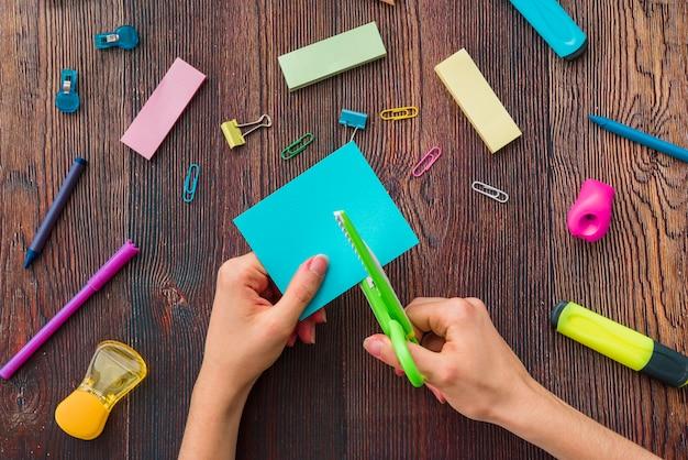 Osoby ręka ciie błękitnego papier nad szkolnymi akcesoriami na drewnianym stole Darmowe Zdjęcia