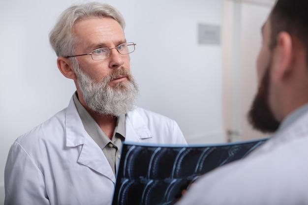 Osoby W Podeszłym Wieku Mężczyzna Lekarz Omawiający Mri Pacjenta Ze Współpracownikiem Premium Zdjęcia
