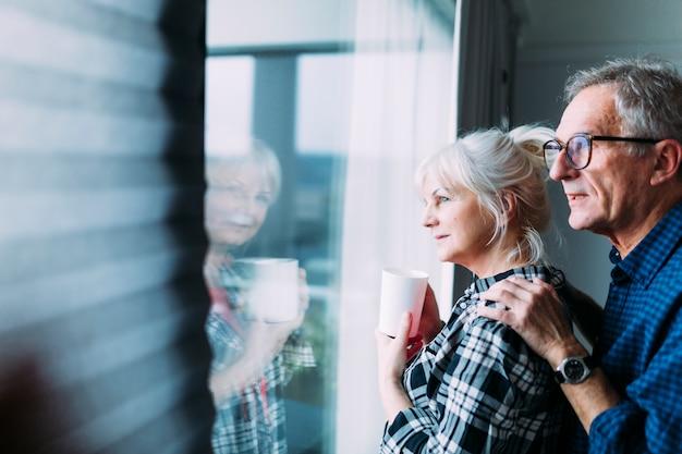 Osoby W Podeszłym Wieku Para W Domu Spokojnej Starości Patrząc Z Okna Premium Zdjęcia