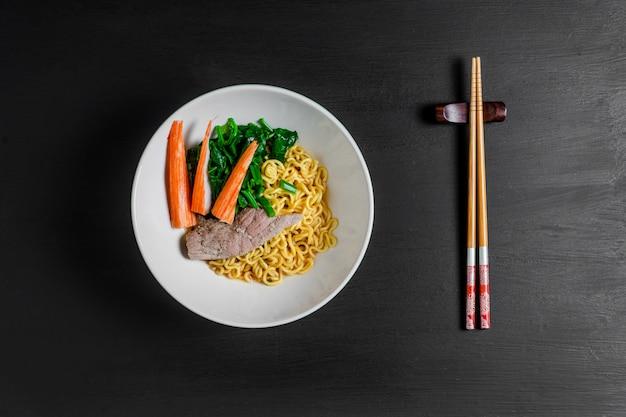 Ostry makaron instant z pałkami z wołowiny i kraba. widok z góry Premium Zdjęcia