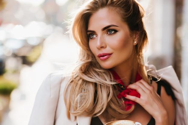 Oszałamiająca Europejska Dziewczyna Z Efektownym Makijażem, Odwracając Wzrok, Dotykając Jej Czerwonego Szalika. Close-up Portret Pięknej Jasnowłosej Kobiety O Niebieskich Oczach Relaksujący Darmowe Zdjęcia