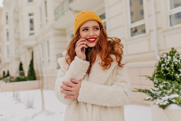 Oszałamiająca Rudowłosa Dama Uśmiechnięta Podczas Pozowania Z Telefonem. Odkryty Strzał Atrakcyjnej Kobiety Imbir Stojącej Na Ulicy W Zimowy Poranek. Darmowe Zdjęcia