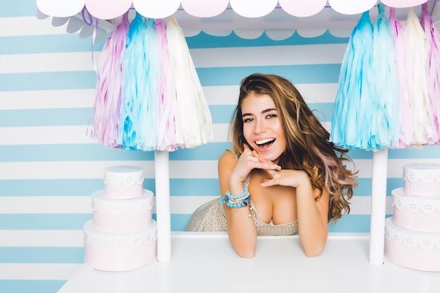 Oszałamiająca Uśmiechnięta Dziewczyna O Wielkich Miłych Oczach Sprzedająca Pyszne Ciasta Stojąca Za Różowym Kontuarem. Szczegół Portret Atrakcyjnej, Radosnej Młodej Kobiety Pozuje Ze Słodyczami Na Niebieskiej ścianie W Paski. Darmowe Zdjęcia