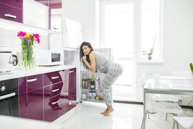 Oszust Diety. Kobieta W Kuchni W Pobliżu Lodówki. Kobieta Chce Jeść. Głodna Pani Rano. Premium Zdjęcia