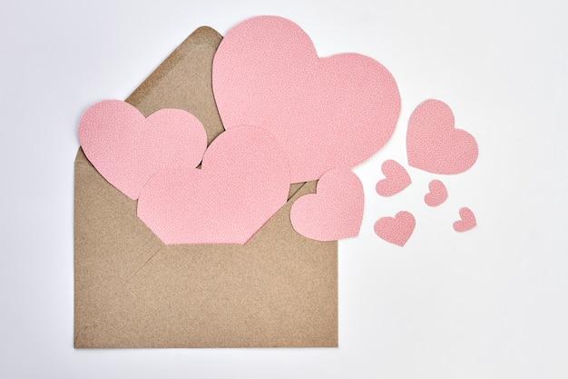 Otwarta Koperta I Różowe Papierowe Serca. Walentynki Koperta Z Papieru Rzemieślniczego I Ozdobnych Serc Na Białym Tle. Wyraź Swoją Miłość Listem. Premium Zdjęcia