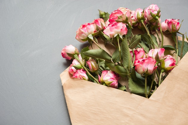 Otwarta Koperta Rzemieślnicza Z Różowymi Różami Na Neutralnej Szarości, Widok Z Góry. świąteczny. Karta Walentynkowa. Premium Zdjęcia
