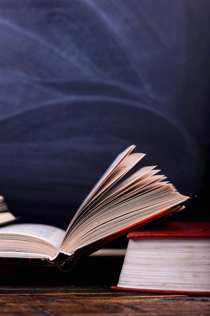 Otwarte książki to stos na biurku, na tle tablicy kredowej. trudna praca domowa w szkole, góra wiedzy. Premium Zdjęcia