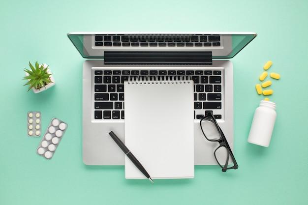 Otwarty laptop z pigułkami i dzienniczkiem na zieleni powierzchni Darmowe Zdjęcia