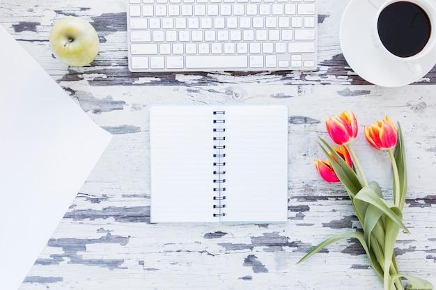 Otwarty notatnik i kwiaty tulipanów w pobliżu klawiatury i filiżanki kawy na odrapanym biurku Darmowe Zdjęcia