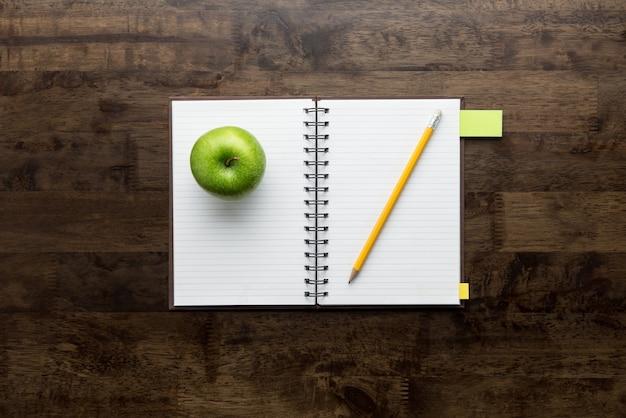 Otwiera notatnika z jabłkiem i ołówkiem na drewno stole Premium Zdjęcia