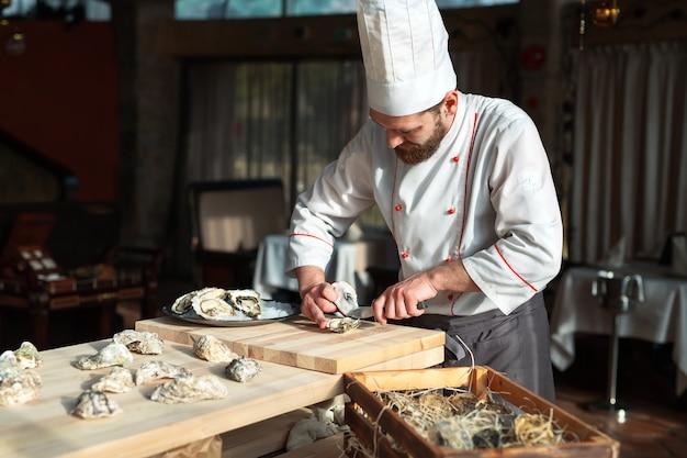 Otwieranie Pustych I Płaskich Ostryg. Szef Kuchni Otwiera Ostrygi W Restauracji. Premium Zdjęcia