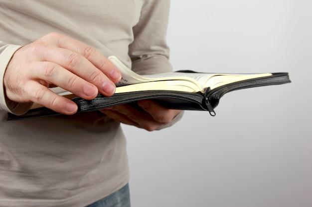 Otwórz Księgę Biblii W Rękach Mężczyzn Premium Zdjęcia
