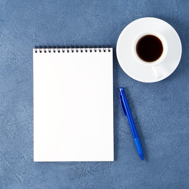 Otwórz notatnik czystą białą stronę, długopis i filiżankę kawy na wieku granatowy stół z kamienia, widok z góry Premium Zdjęcia