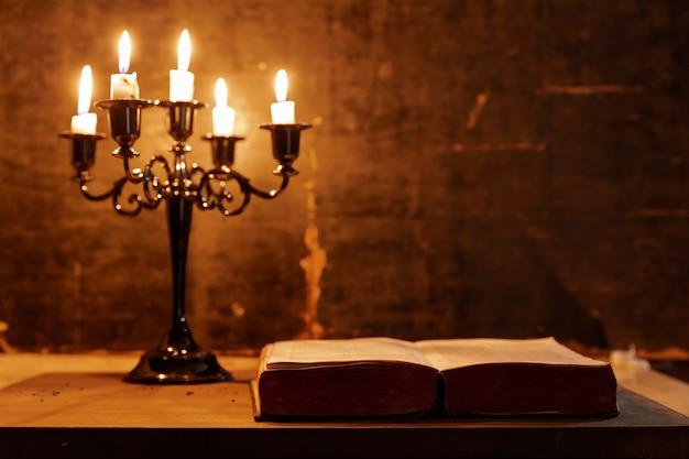 Otwórz świętą biblię i świecę na starym dębowym drewnianym stole. piękne złote tło. koncepcja religii. Darmowe Zdjęcia